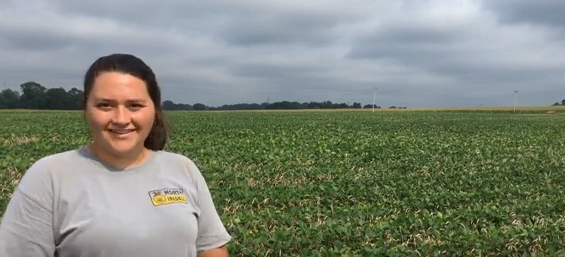 Female standing out in a field of soybeans, smiling